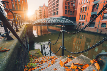 Speicherstadt warehouse district in Hamburg, Germany. Old brick buildings and channel of Hafencity quarter on autumn evening with sunset golden flares