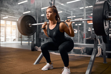 beautiful sporty weightlifter holding heavy metal professional barbell, preparing to stand and make exercise called deadlift, side shot, portrait