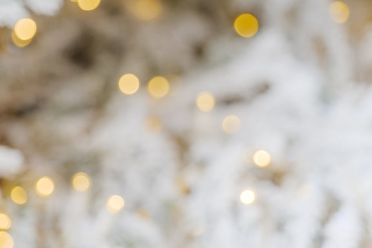 Defocus close up view of Illuminated abstract round gold bokeh on blur white background. Golden glitter bokeh from out of focus view of decoration bulbs on white Christmas tree.