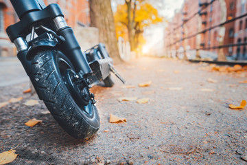 Close up of e-scooter front wheel tire parked outdoor in autumn season. Hamburg, Germany, Europe