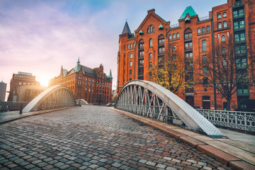Arch bridge over alster canals with cobbled road in historical Speicherstadt of Hamburg, Germany, Europe. Scenic view of red brick building lit by golden sunset light