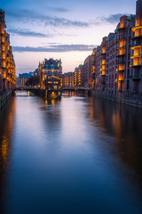 Hamburg city old port during blue hour, Germany, Europe. Historical famous warehouse district artificial illuminated. Water castle palace mirrored on river surface. Vertical orientation