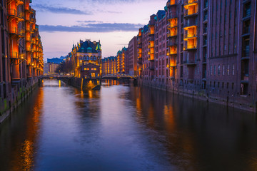 Hamburg city old port during blue hour, Germany, Europe. Historical famous warehouse district artificial illuminated. Water castle palace mirrored on river surface