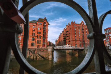 Speicherstadt warehouse district in Hamburg, Germany, Europe. Old brick buildings and channel of Hafencity quarter. UNESCO heritage. Shoot thought cast-iron creative concept