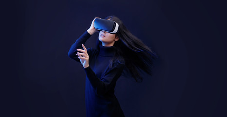 Wall Mural - Beautiful woman with flowing hair in futuristic dress over dark background. Girl in glasses of virtual reality. Augmented reality, game, future technology concept. VR. Free space for text.
