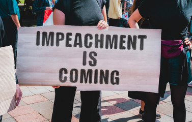 "The phrase "" Impeachment is coming "" drawn on a carton banner. A girl holds a cardboard with an inscription. Girls on the street. Politics. Power. Government"