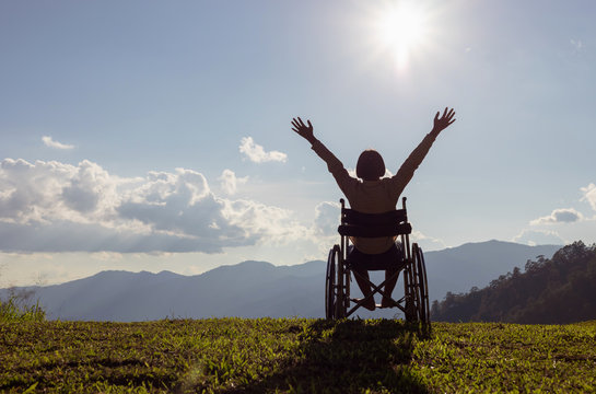 Happy disabled child in a wheelchair and stretching hands at sunset. back view,