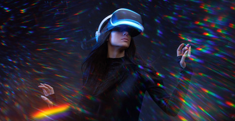 Wall Mural - Beautiful young woman using VR helmet while touching air in colorful rainbow neon lights. Girl in glasses of virtual reality with blue backlight with flowing hair over dark magic universe background.
