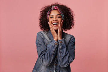 Joyful attractive young curly brunette woman with dark skin wearing casual hairstyle, having colorful headband on her head and holding face with raised palms, isolated over pink background