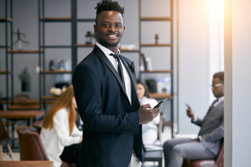 Personable businessman wearing formal black tuxedo stand posing in office environment and look at camera and smile . Using smartphone in working time. Business people concept