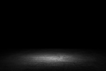 Black background with spotlight to concrete ground in studio. Dark interior background. Room with tile or cement and concrete floor..