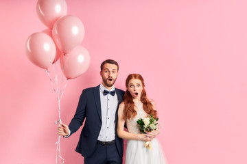 wedding couple posing together isolated over pink background. man in tuxedo holding pink air ballons, woman in white wedding dress bouquet. Woman with auburn hair, couple with opened mouth