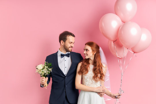 Handsome man in tuxedo and redhaired woman in wedding dress look at each other with love. Holding pink air balloons and bouquet, pink background. Man and woman in love look at each other