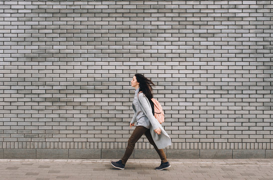 Young beautiful caucasian woman in gray pullover with a pink bag walking on the autumn street. Brick wall.