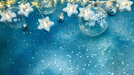 festive new year snowy blue background with various christmas tree decorations and glowing christmas lights