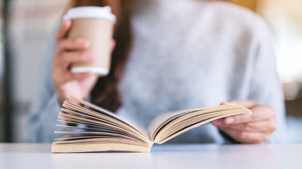 Closeup image of a woman holding and reading a book while drinking coffee on wooden table