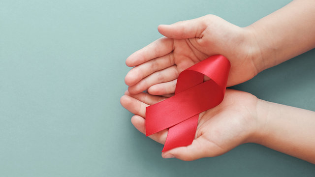 Hands holding red ribbon on red background, hiv awareness concept, world AIDS day, world hypertension day