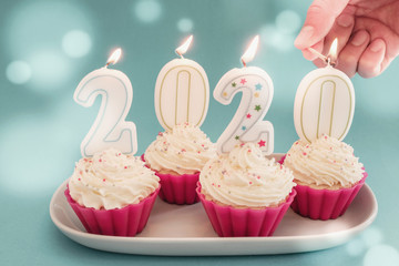 2020 candles on cupcakes with whip cream frosting using pink silicone reusable cups on blue fairy lights background, Happy New year sweet food concept