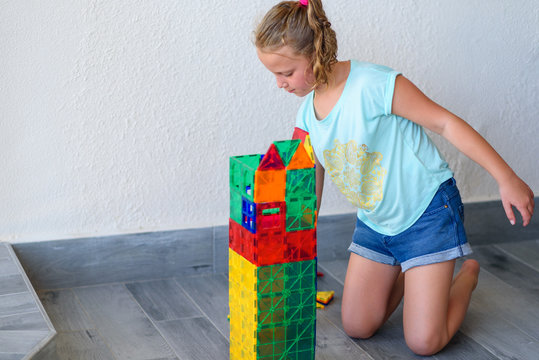 Beautiful teenage girl playing with lots of colorful plastic blocks constructor and builds house.