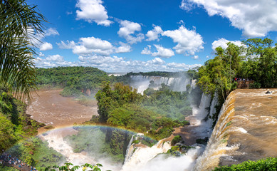 Scenic view from top of the waterfalls with a rainbow to Iguazu river and San Martin Island, blue sky and white clouds, Iguazu Falls, Argentina
