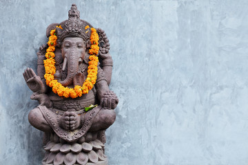 Printed kitchen splashbacks Bali Ganesha sitting in meditating yoga pose in front of hindu temple. Decorated for religious festival by orange flowers garland, ceremonial offering. Balinese travel background. Bali island art, culture.