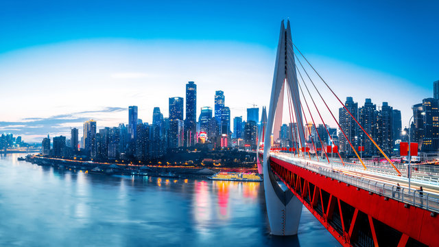cityscape and skyline of downtown near water of chongqing at sunset