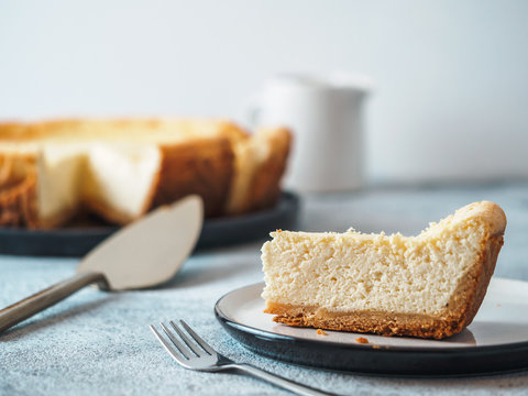 Plate with piece of cheesecake on tabletop. Classic homemade cheesecake with Shallow DOF. Copy space for text.