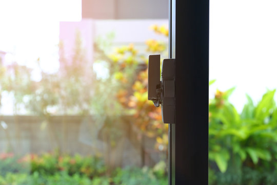 security lock on glass window with green garden outside view of home