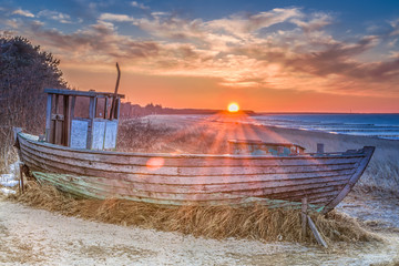 schöner alter Fischkutter am Strand der Seebrücke Zingst zum Sonnenuntergang