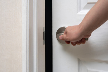 Men's hand opens and closes the door.