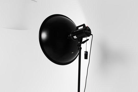 beauty dish studio flash mounted on a flash unit on a lighting workshop, turned on modelling light