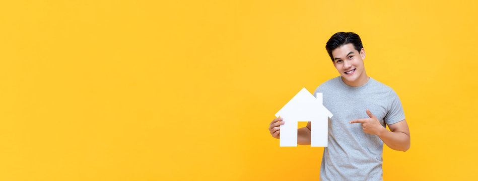 Handsome Asian man smiling and pointing to new house cutout