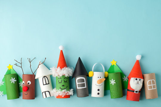 Paper toy Santa, Snowman, Grinch for Xmas party. Easy crafts for kids on blue background, copy space, die creative idea from toilet tube roll, recycle reuse eco concept