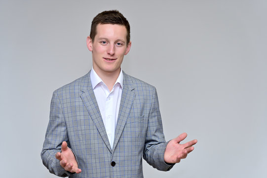 Concept of a pleasant young man manager talking to the camera.Photo Portrait of a secretary guy on a gray background in a gray business suit and white shirt in various poses.