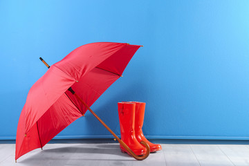 Wall Mural - Beautiful red umbrella and rubber boots near blue wall. Space for text