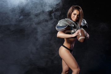 american football woman player with ball on dark smoke  background. athletic brunette fitness sexy girl as rugby player