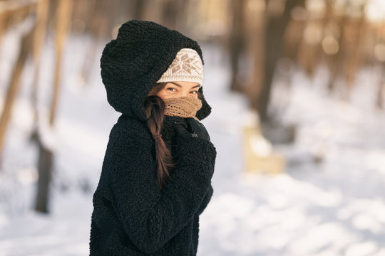 Cold winter protection Asian woman protecting skin covering nose and mouth with warm scarf - cold weather clothes accessories outdoor people lifestyle.