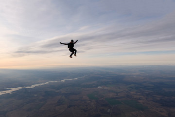 Skydiving. A solo skydiver is flying in the sky