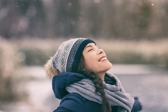 Winter woman happy enjoying snow falling on face outdoor forest nature Asian girl looking up wearing hat and scarf cold weather clothes.