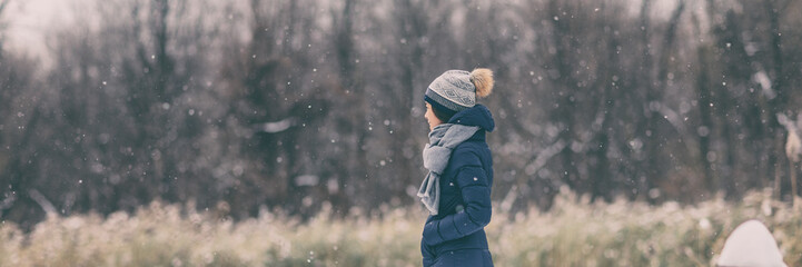 Winter snow forest walk young woman wearing cold weather coat jacket walking in outdoor nature forest relaxing banner panoramic header. Girl wearing hat, scarf, warm clothes.