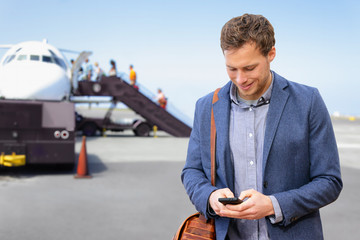 Airport man texting on phone leaving for business trip. Businessman on smartphone boarding plane. Young male professional using 5g data on smartphone app in flight flying wearing suit and laptop bag.
