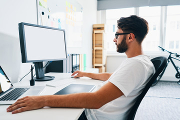 Young man, designer working on computer in office