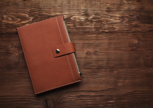 Leather diary on a  wooden brown background photo