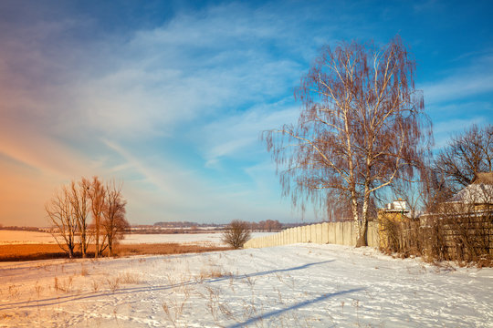 Rural winter landscape. The snow-covered field at the edge of the village