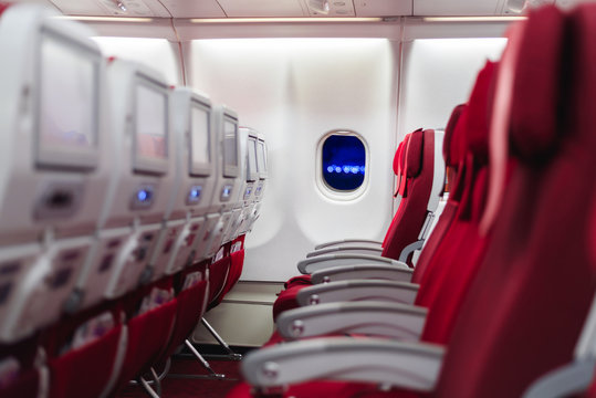 Empty passenger seat in an airplane in red
