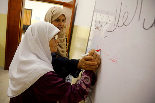 Palestinian woman Seham Somodi, 66, writes on a board as she takes part in a literacy class at Al-Yamoun Community Center in Al-Yamun town in the Israeli-occupied West Bank
