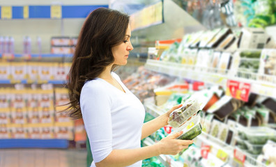 Woman choosing daily products at supermarket. Reading product information. Concept of information...