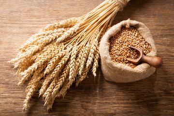 wheat ears and grains on a wooden table,
