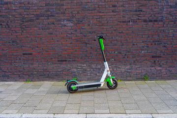 E Scooter vor einer Ziegel Wand