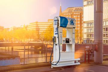 Wasserstoff Tankstelle H2 Tanksäule in der Stadt Hamburg mit Häusern und Sonne im Hintergrund